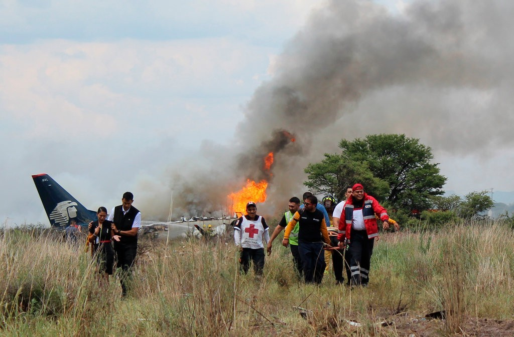 Red Cross workers and rescue workers carried an injured person on a stretcher, right, after an Aeromexico airliner crashed in a field near the airport in Durango, Mexico, on Tuesday. Credit Credit Red Cross Durango